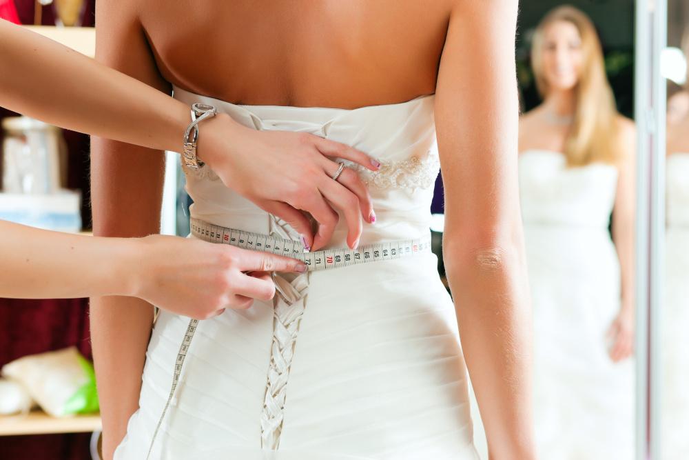 krawcoma mierzy panne mloda ubrana w suknie slubna