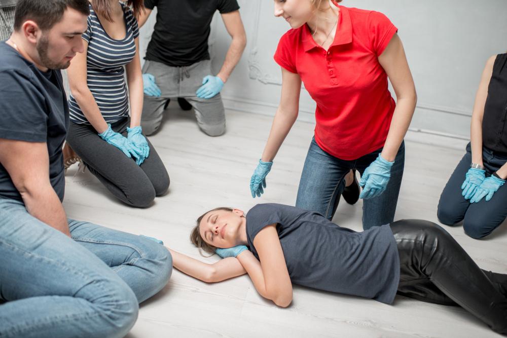 kobieta ktora jest instruktorem bhp pokazuje na przykladzie innej kobiety pozycje boczna ustalona przy innych pracownikach