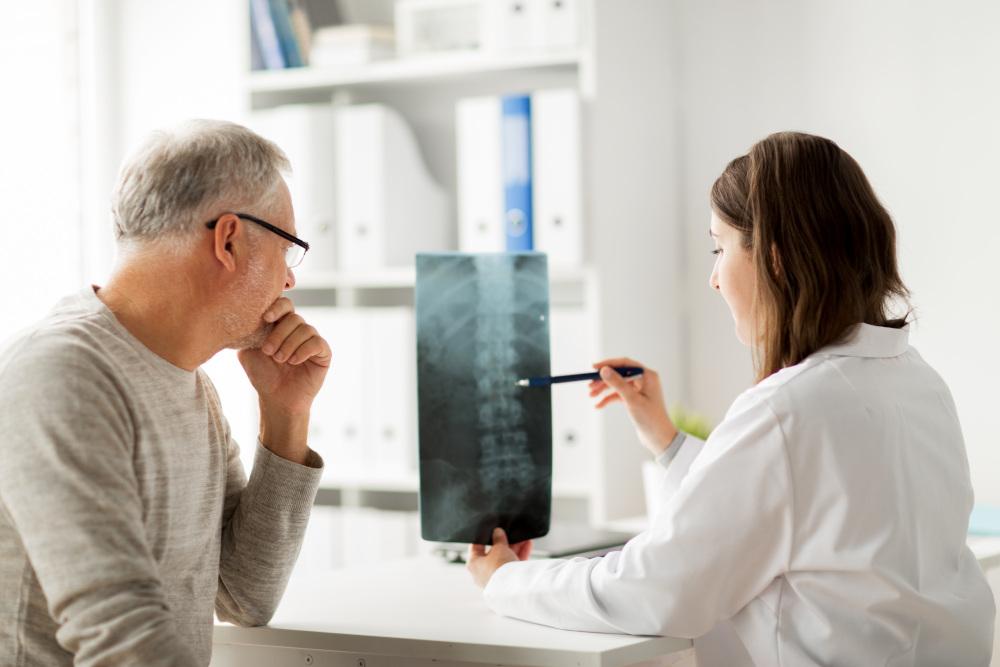 lekarz omawiający zdjęcie rentgenowskie kręgosłupa z pacjentem