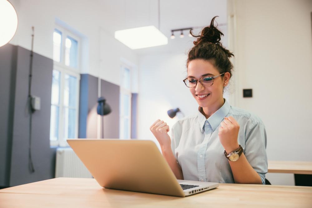 młoda kobieta trzyma laptopa na kolanach